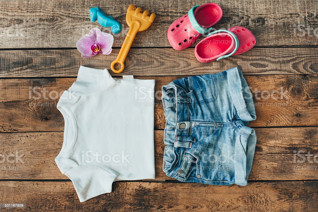 Overhead view of child clothes laid out on wood tabletop. stock photo