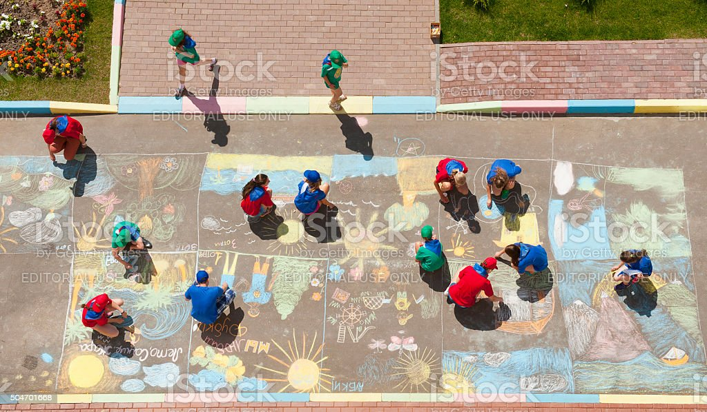 Overhead view of children drawing chalk pictures stock photo