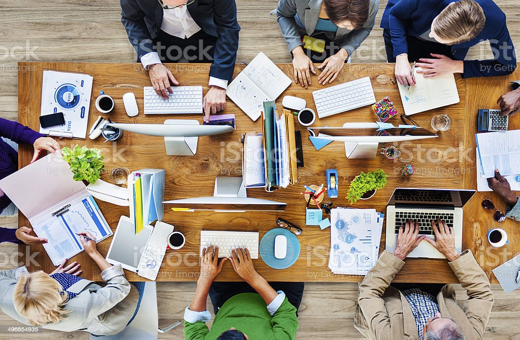 Overhead view of colleagues at work on one table stock photo