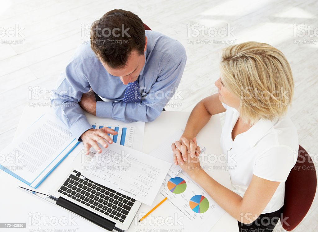 Overhead view of coworkers working at desk overlooking paper royalty-free stock photo