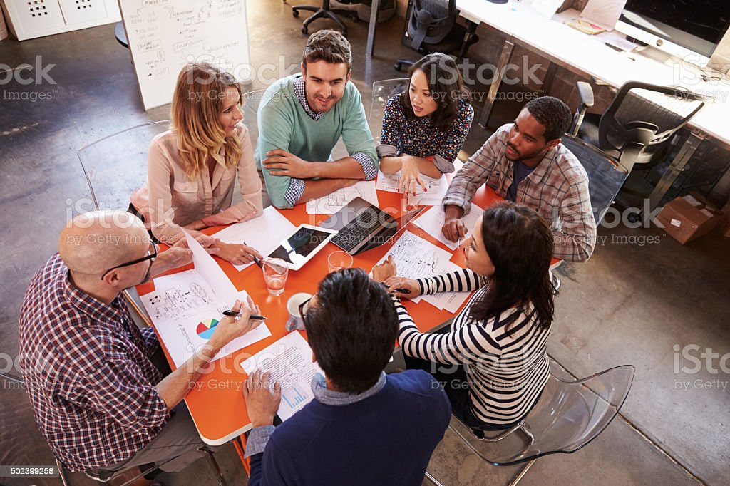 Overhead View Of Designers Having Meeting Around Table stock photo