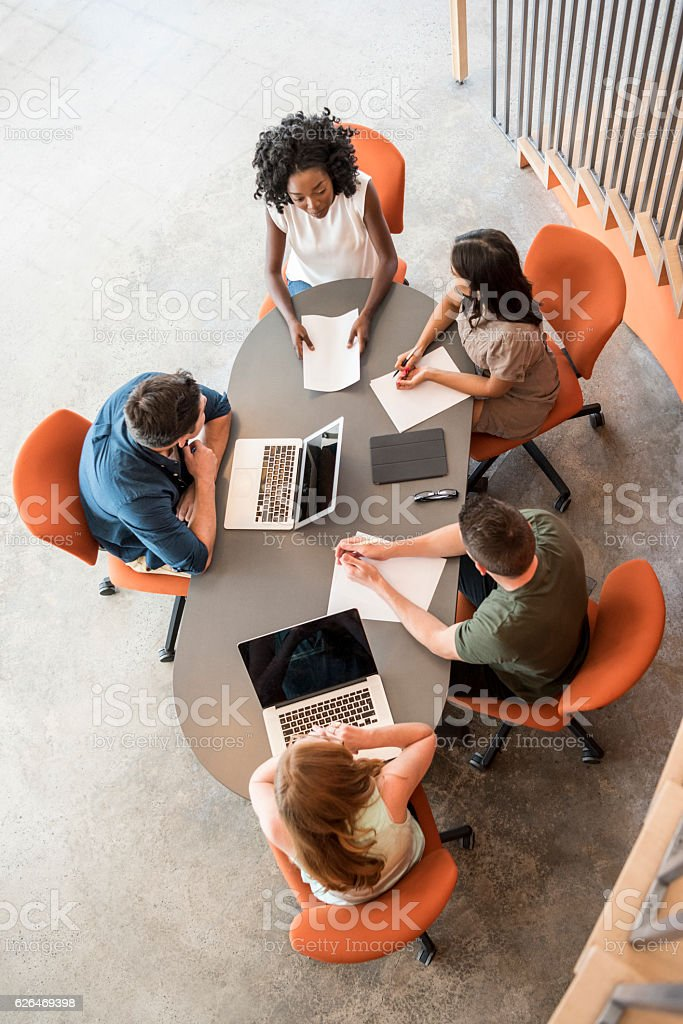 Overhead view of five business people at table in meeting stock photo