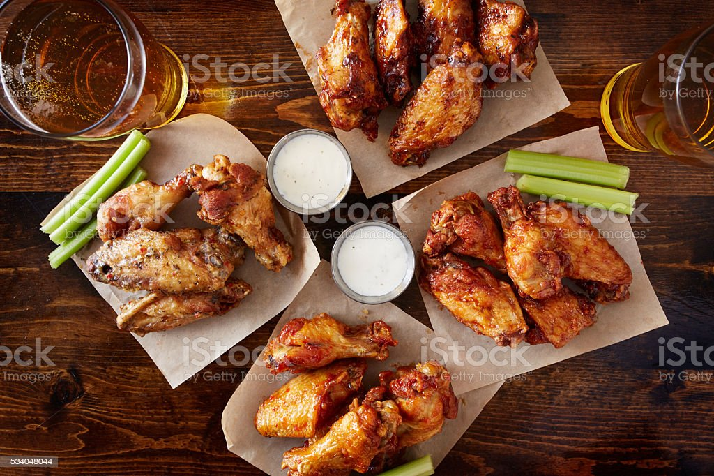 overhead view of four different flavored chicken wings with beer stock photo