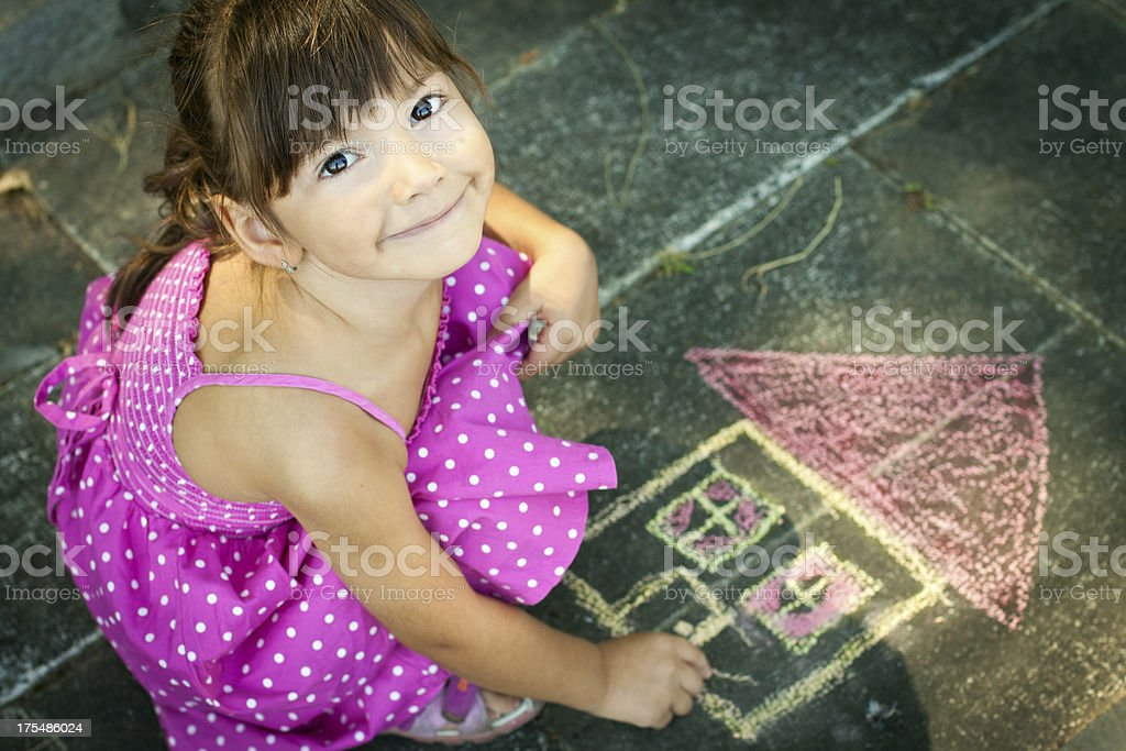 Overhead view of girl drawing on the sidewalk stock photo