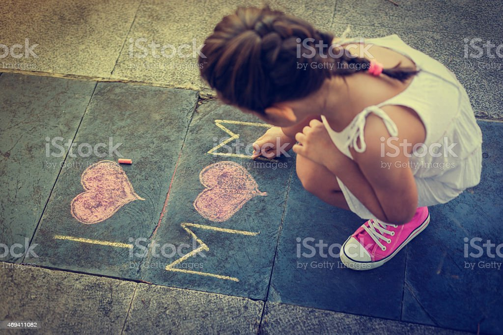 Overhead view of Girl using chalk to write I love mom  stock photo