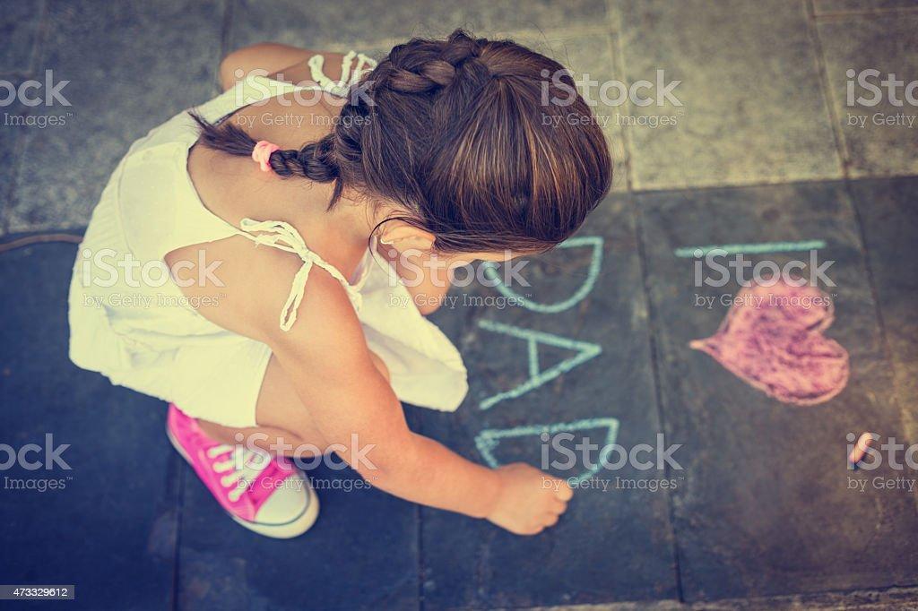 Overhead view of girl writing on the sidewalk stock photo