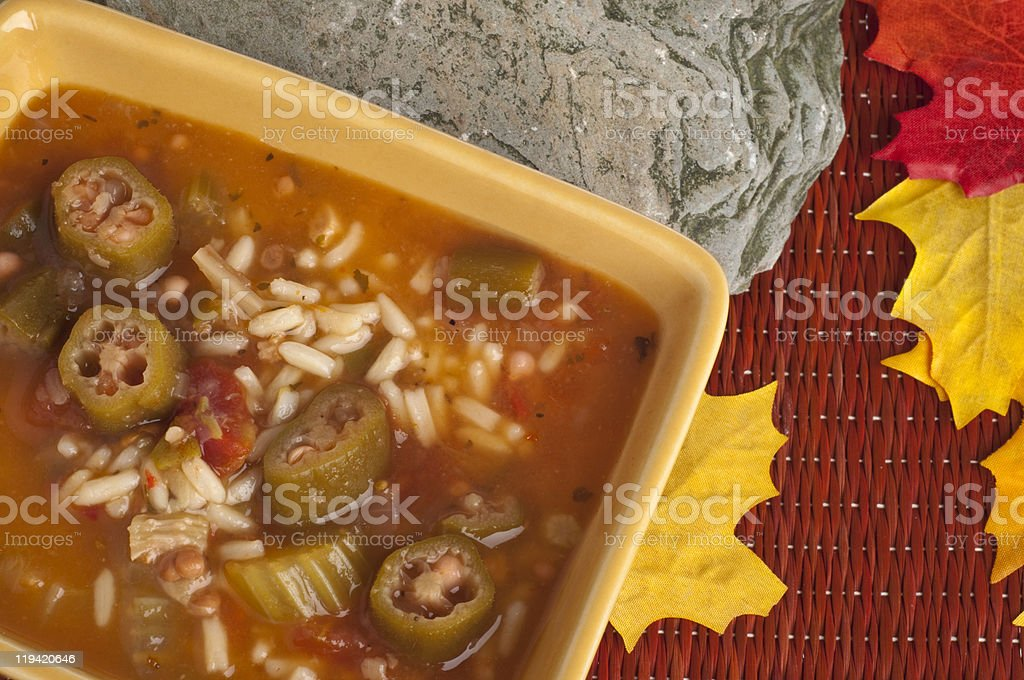 Overhead view of gumbo with okra in a square yellow bowl  stock photo