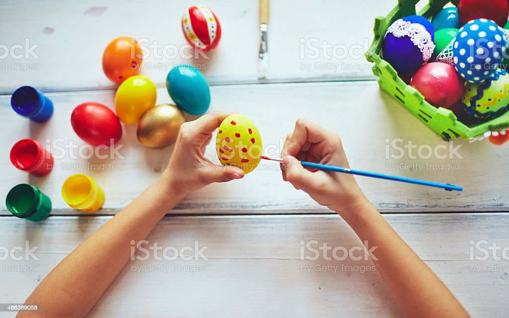 Overhead view of hands painting spotted eggs stock photo