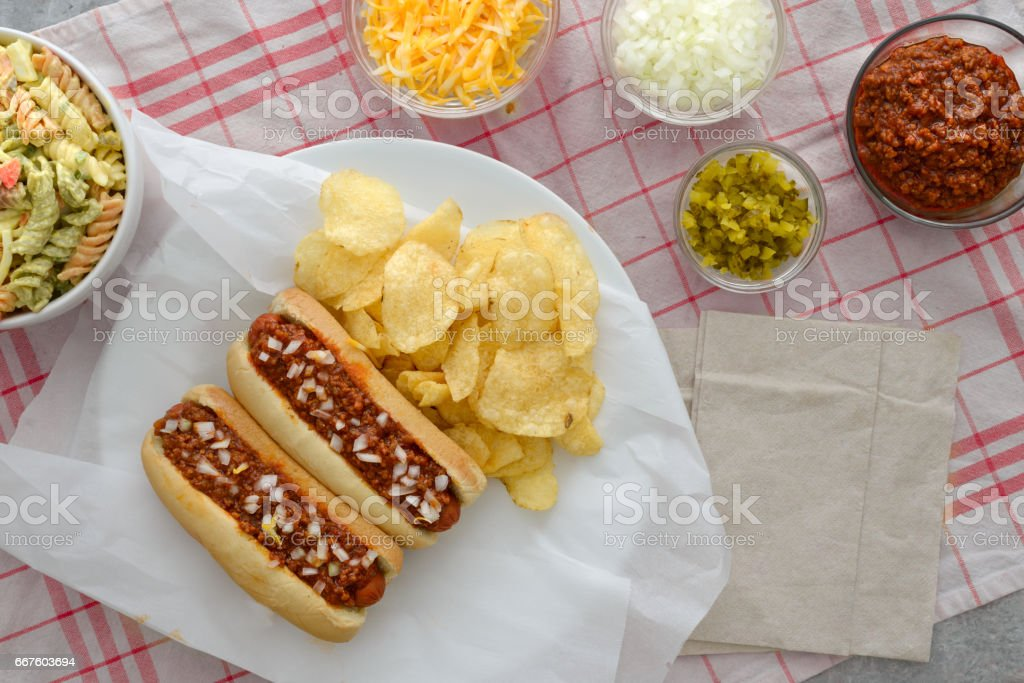 Overhead view of hot dogs, potato chips, macaroni salad and condiments stock photo