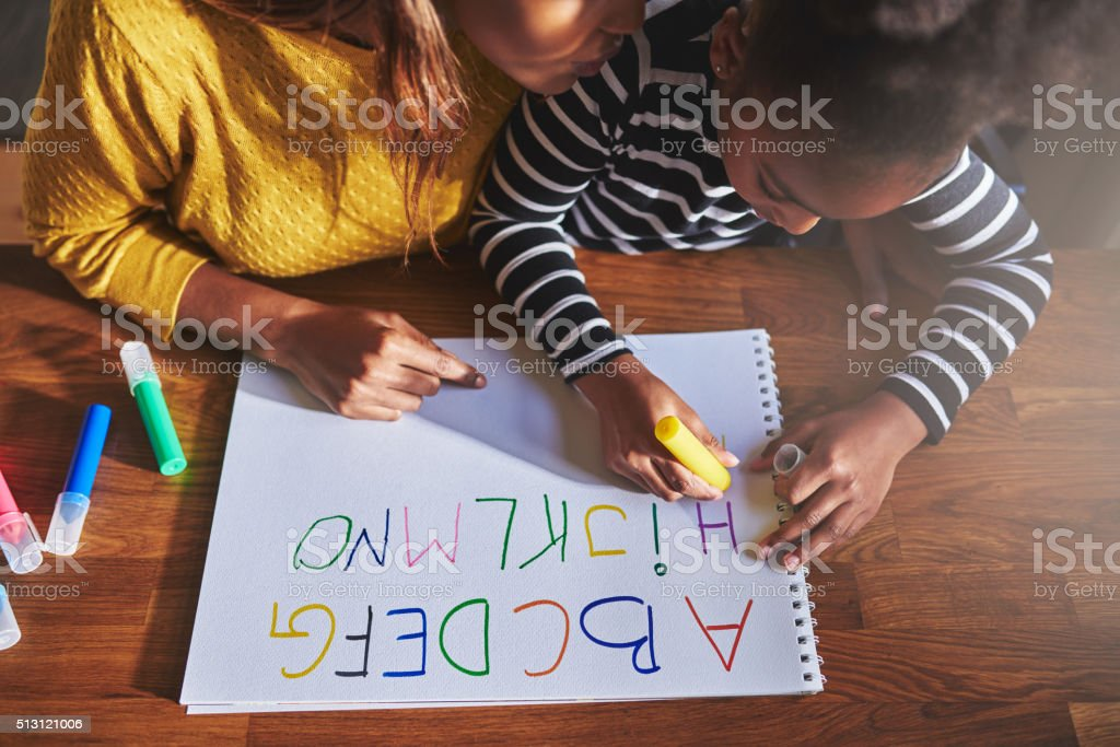 Overhead view of little girl learning the alphabet stock photo