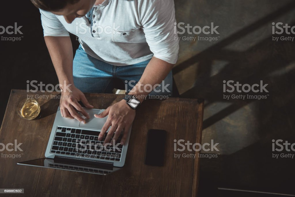 Overhead view of man in casual clothes working on laptop with smartphone and glass of beverage stock photo