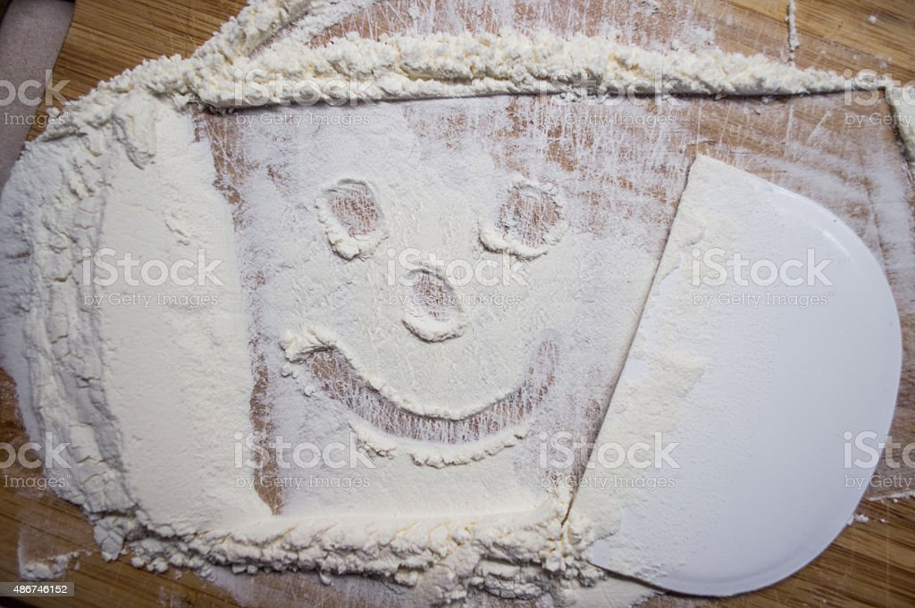 Overhead View of Smiling/Happy Face Drawn into White Flour royalty-free stock photo
