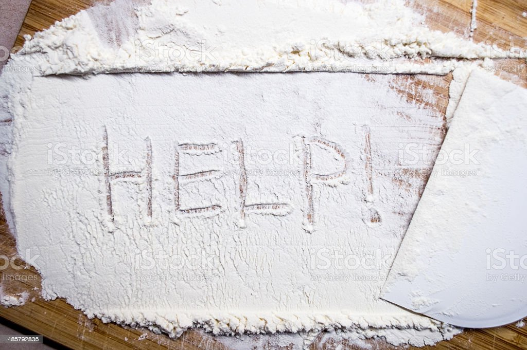 Overhead View of Spread White Flour with 'Help' Drawn royalty-free stock photo