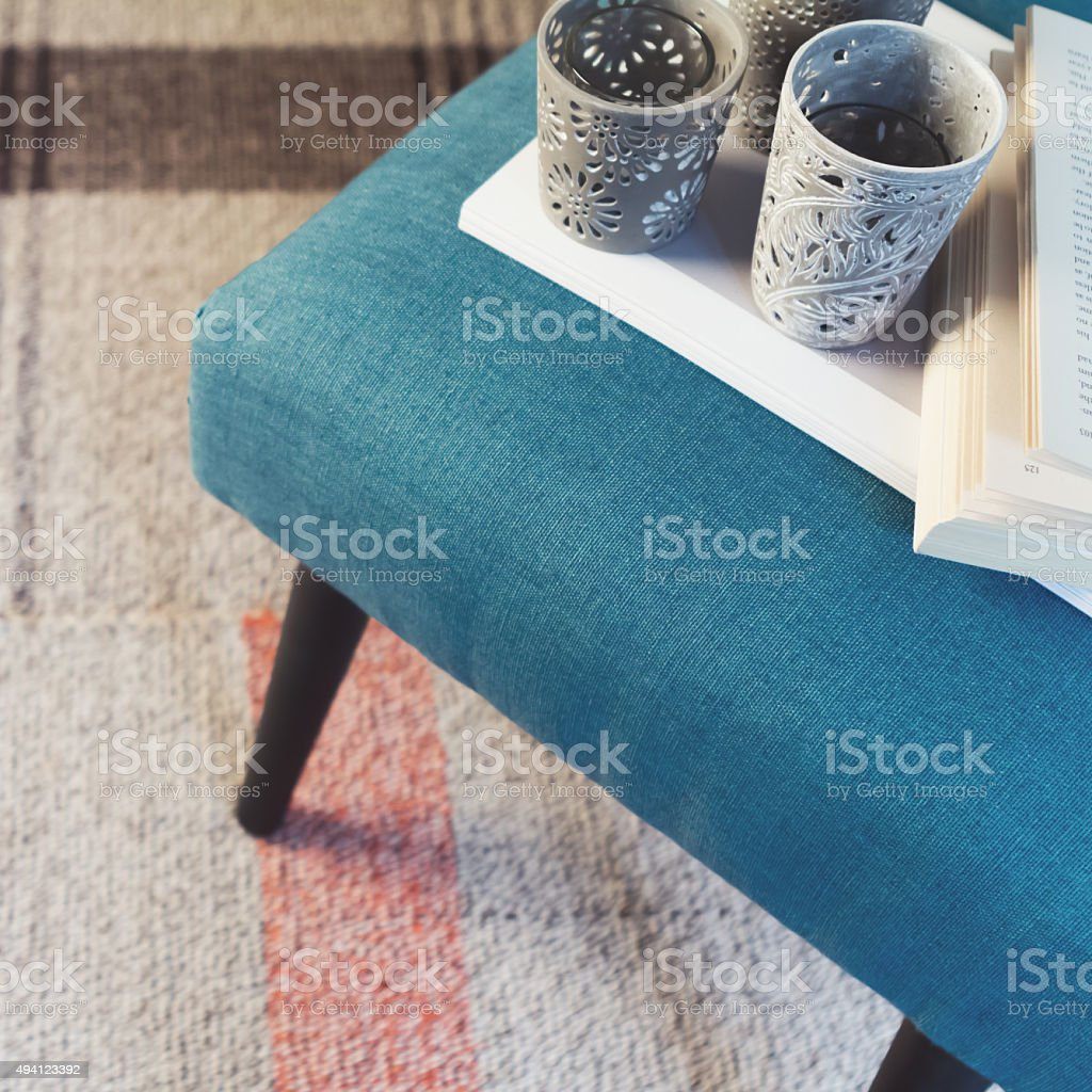 Overhead view of teal ottoman and votive candle holders stock photo