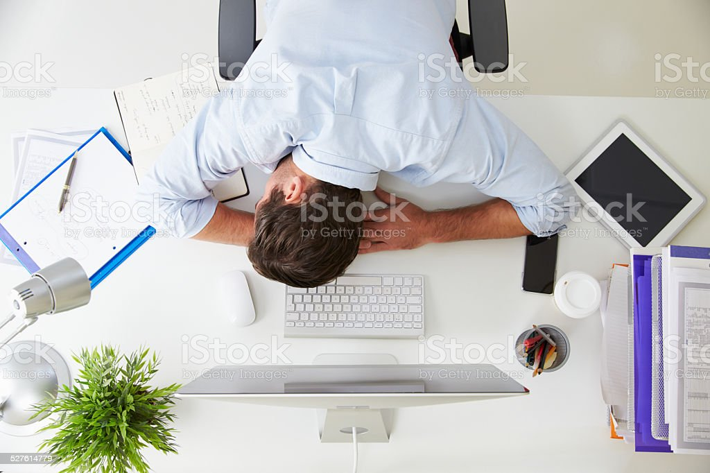 Overhead View Of Tired Businessman Resting By Computer stock photo