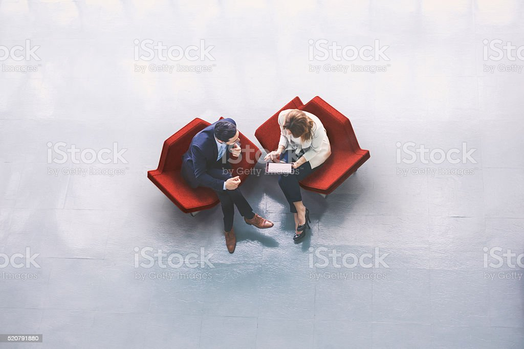 A high-angle view of a businessman and a businesswoman sitting in the...