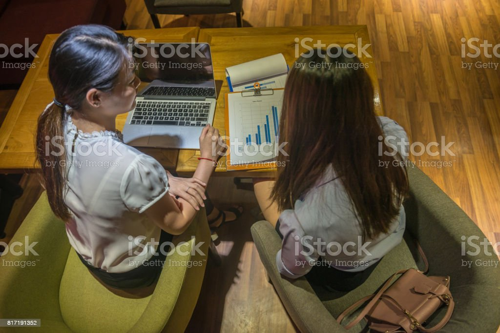 Overhead view of two businesswomen working late, discuss about work stock photo