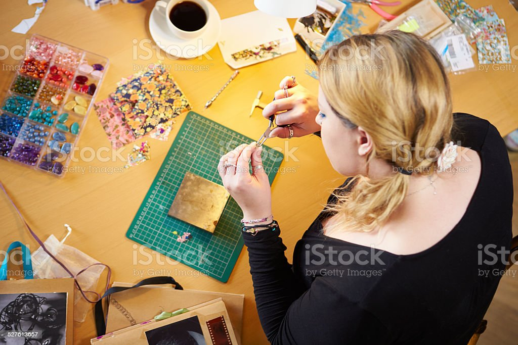 Overhead View Of Woman Making Jewelry At Home stock photo