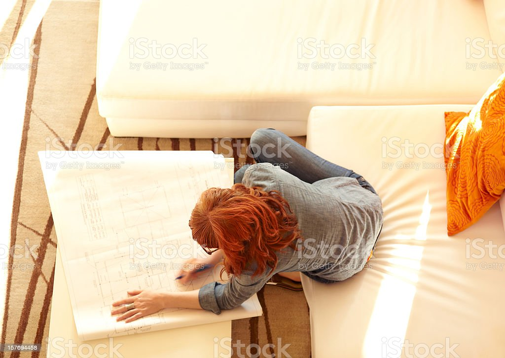 Overhead view of woman reviewing architecture plans at home stock photo