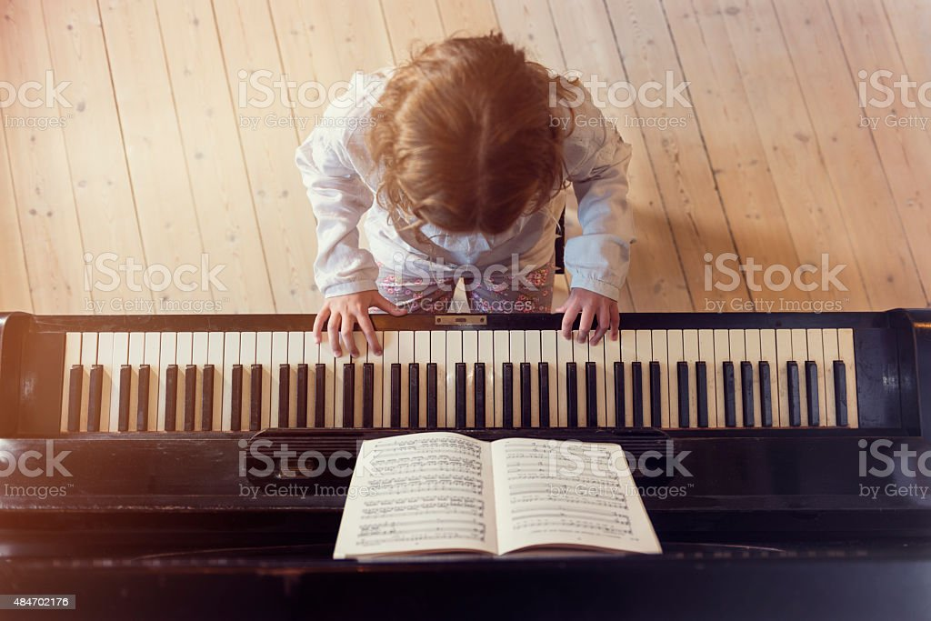 Overhead View of Young Girl Playing Piano In Sunlight Room stock photo