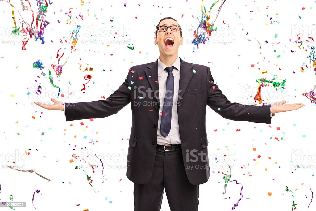 Overjoyed businessman with confetti around him stock photo