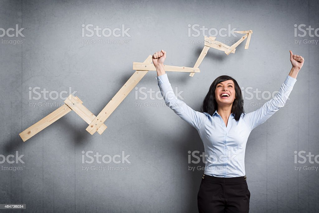 Overjoyed businesswoman in front of ascending business graph. stock photo