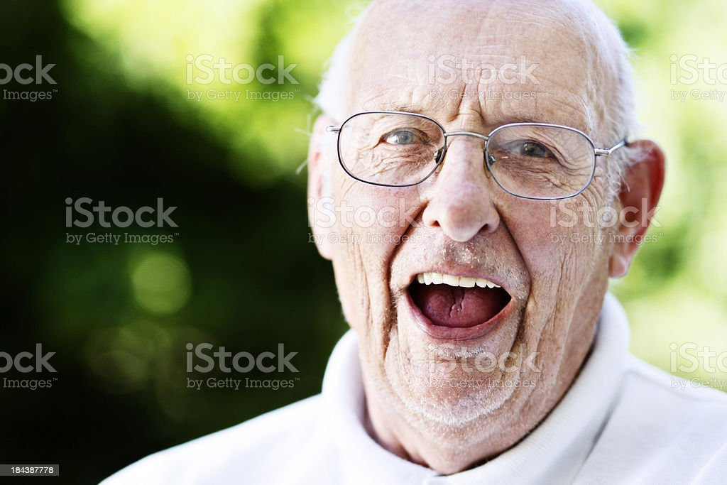 Overjoyed old man laughs in his garden royalty-free stock photo