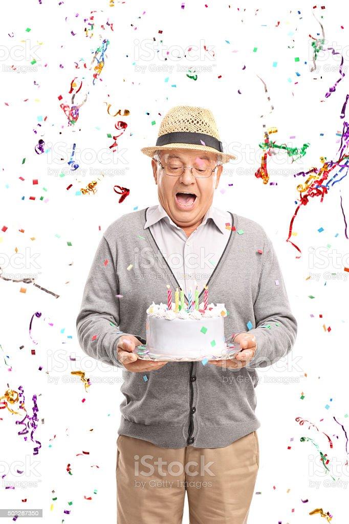 Overjoyed senior holding a birthday cake stock photo