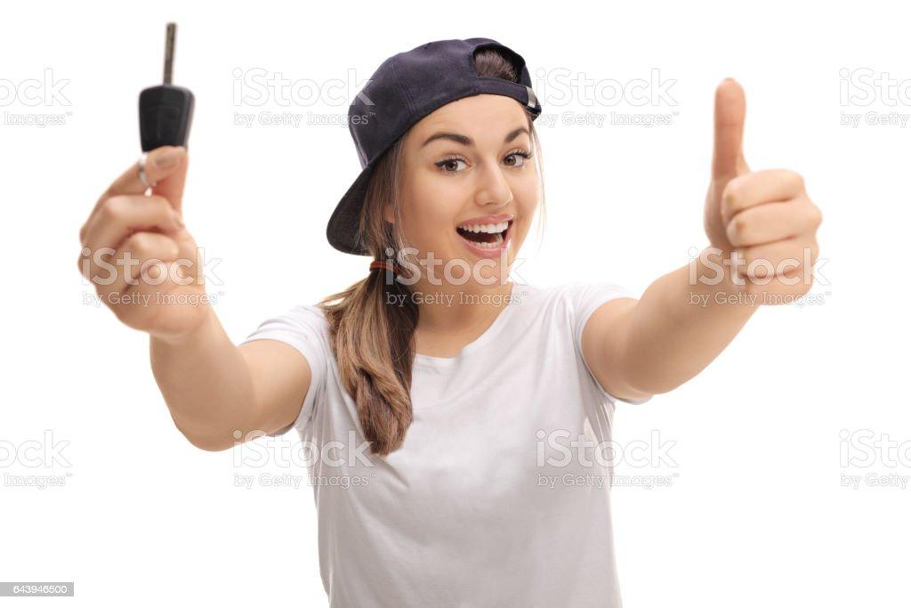 Overjoyed teenage girl holding car key and thumb up stock photo