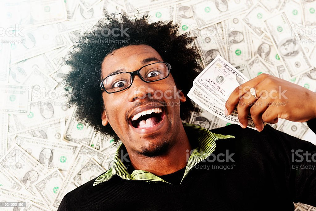 Overjoyed young man with fistful of dollars lying on money stock photo