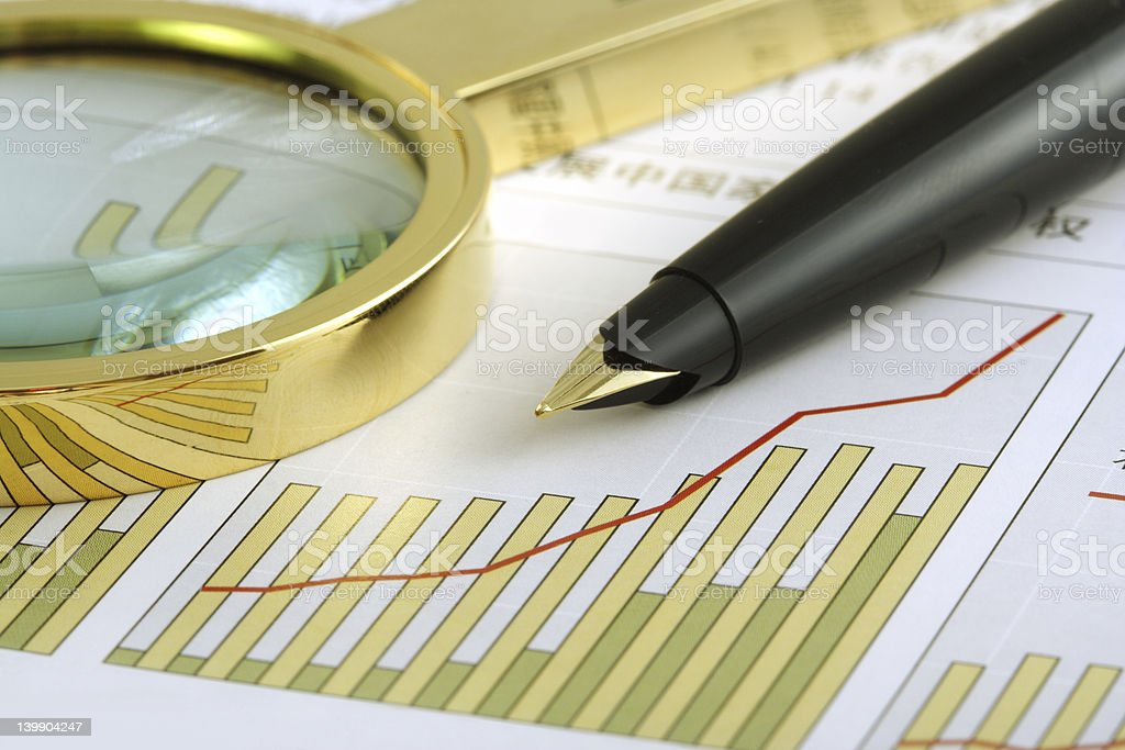 Overlapping bar and line graph with pen and magnifying glass royalty-free stock photo
