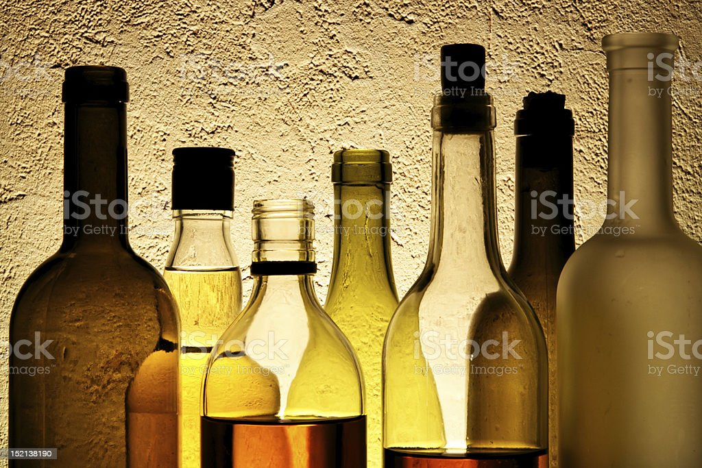 Overlapping bottles of alcohol against a textured wall royalty-free stock photo