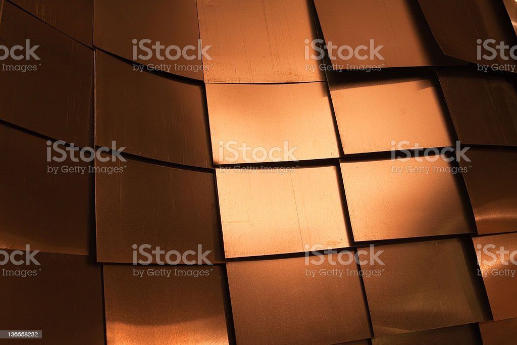 Overlapping bronze plates background stock photo