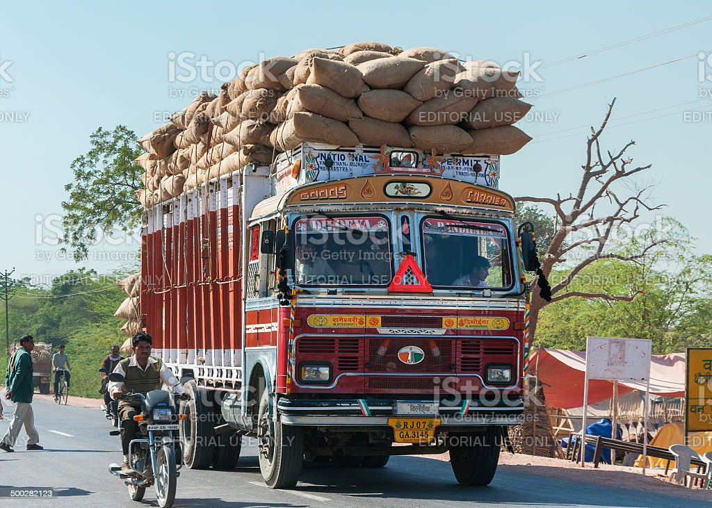 Overloaded dump truck riding on rural road. stock photo