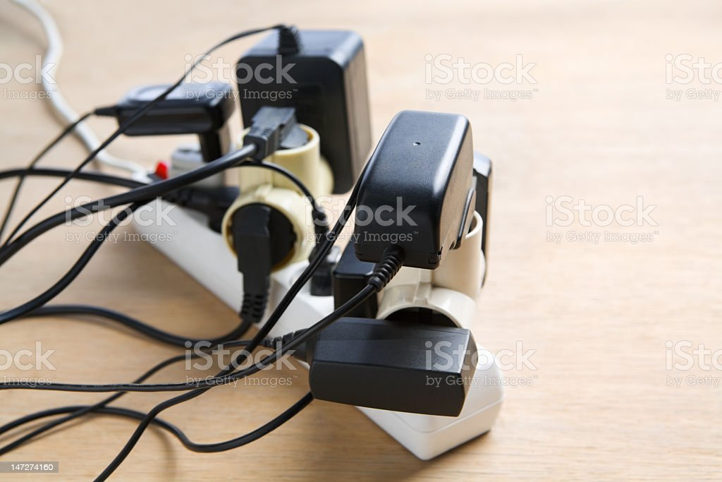 Overloaded extension cord with many plugs attached stock photo
