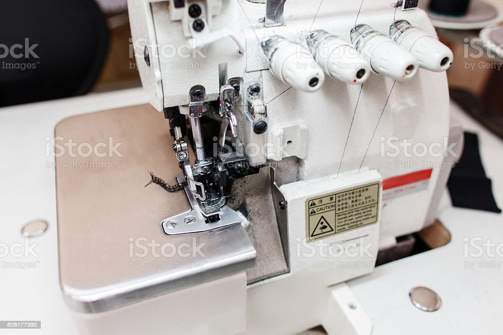 Overlock sewing machine in tailor office close-up stock photo