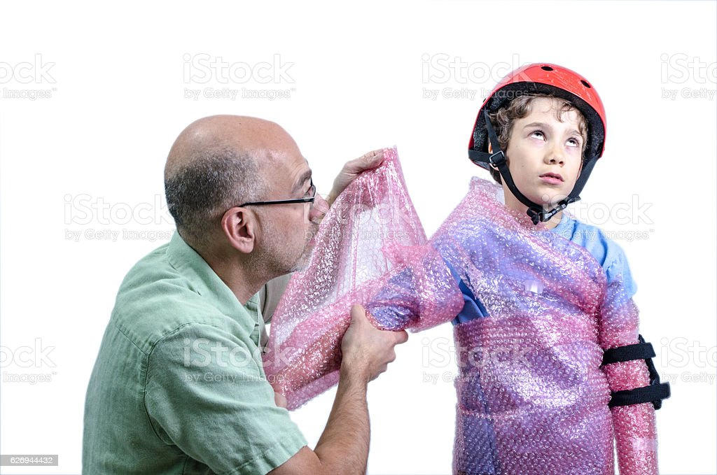 Overprotecting dad putting plastic bubbles over kid before skatebording stock photo
