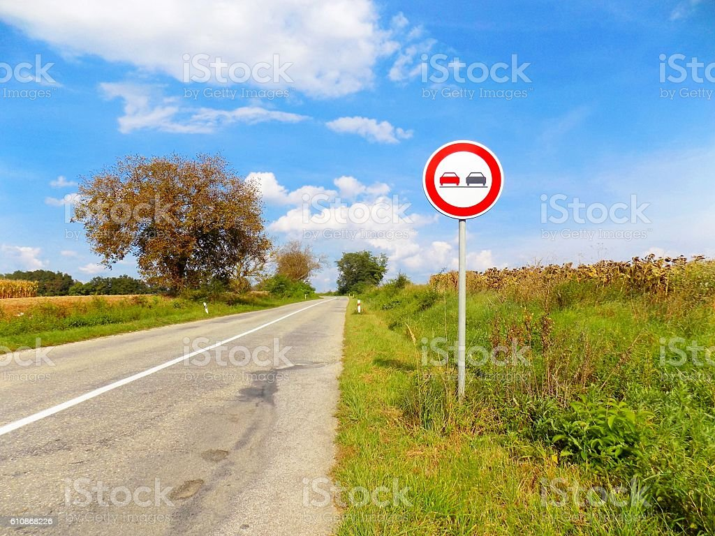 Overtaking roadsign near asphalt road in nature during sunny day stock photo