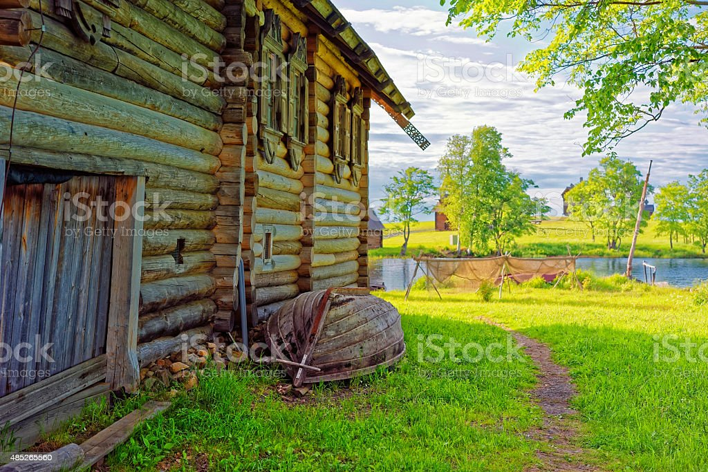 Overthrown boat near old log built hose at Kizhi site stock photo