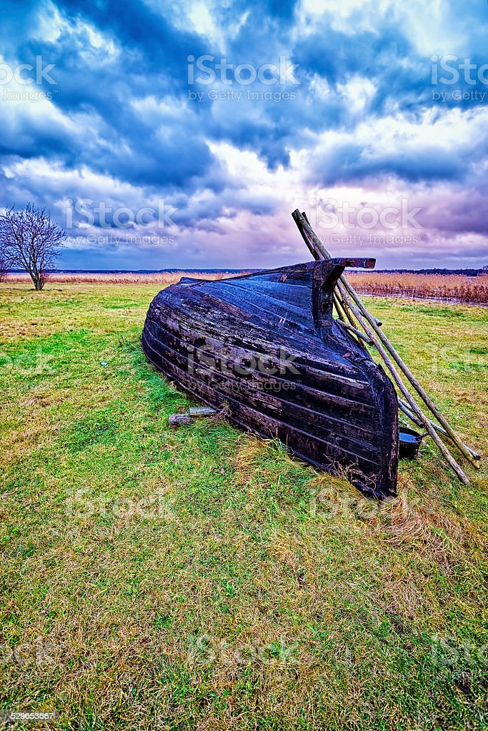 Overthrown fisherman boat on the lake shore at stormy weather stock photo