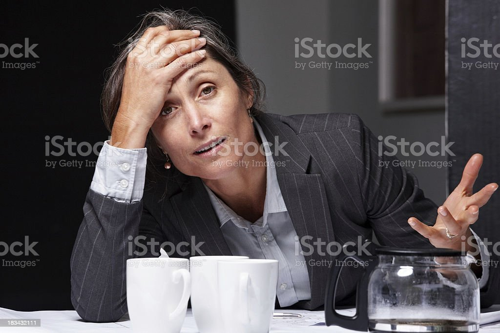 Overtime concept - Business woman getting tired of her work royalty-free stock photo