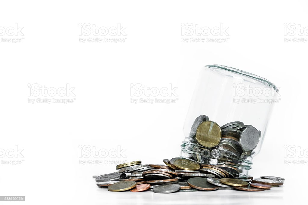 Overturn glass jar with coins spilled out, on white background stock photo