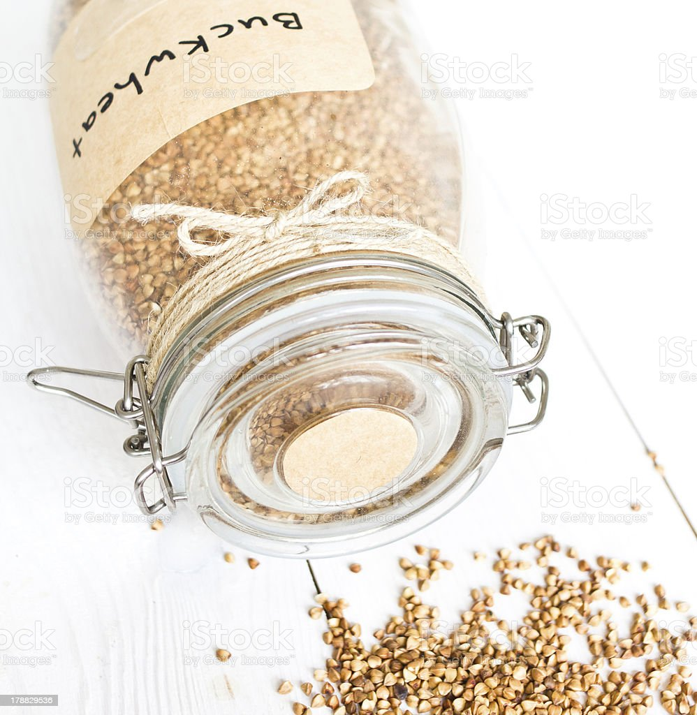 Overturned  glass jar with grains  on a white wooden background royalty-free stock photo