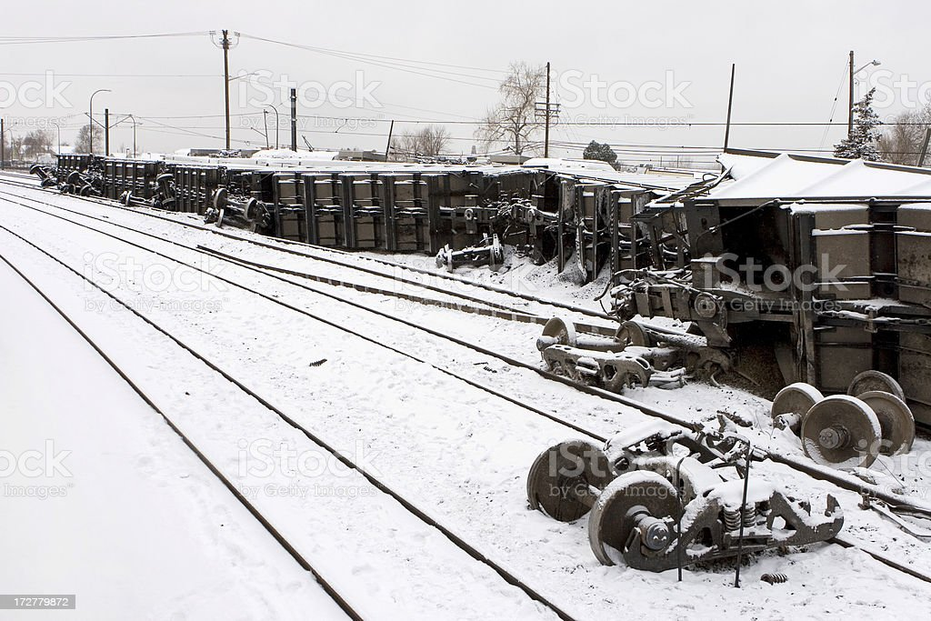 Overturned train in snow with tracks, wheels, cars stock photo