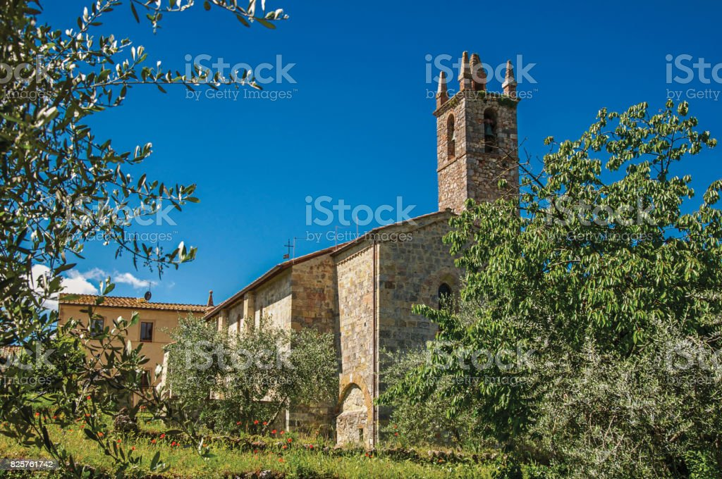 Overview of church and bell tower with trees around in the hamlet of Monteriggioni. stock photo