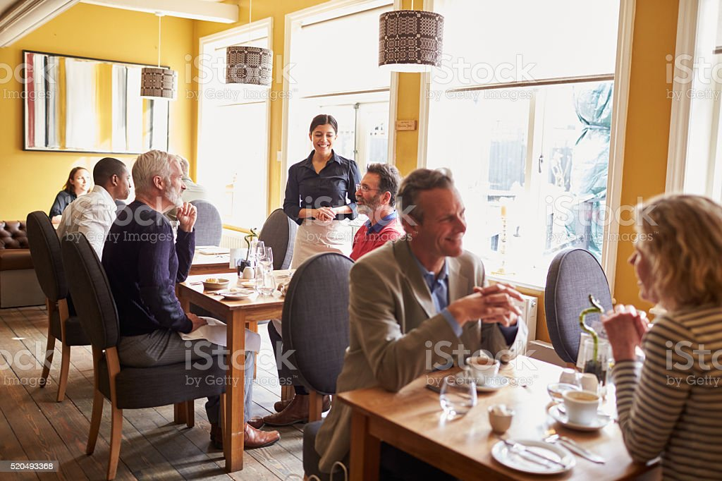 Overview of customers and a waitress in restaurant interior stock photo
