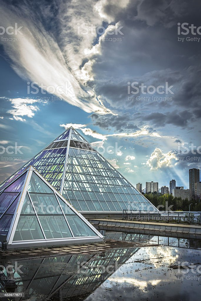 Overview of glass pyramids against cloudy skies stock photo