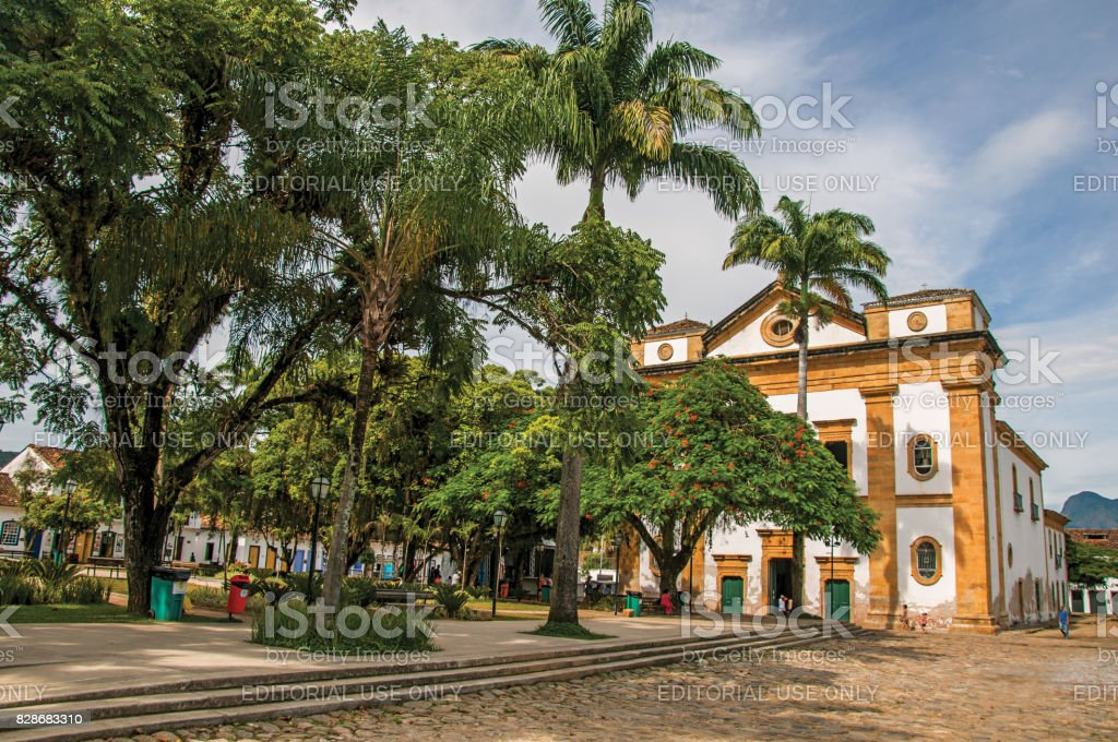 Overview of old colored church, garden with trees and cobblestone street in Paraty. stock photo