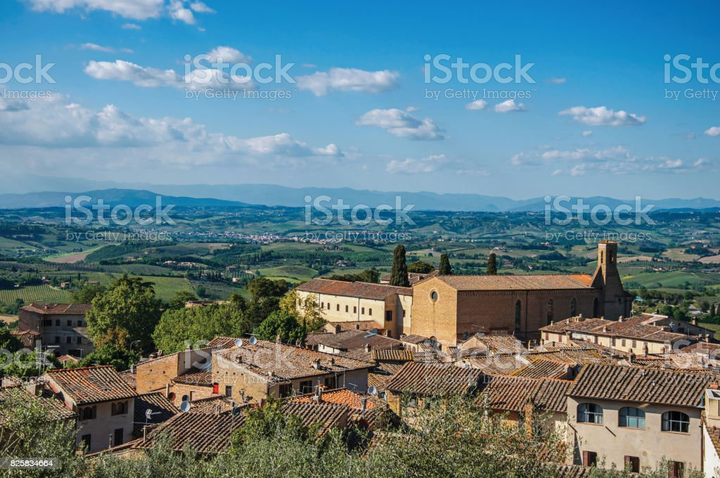 Overview of rooftops and church with green hills and blue sky at San Gimignano. stock photo