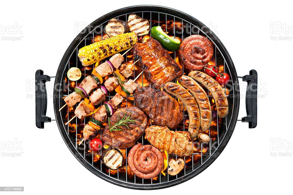 Overview of various meats and vegetables on a round grill stock photo